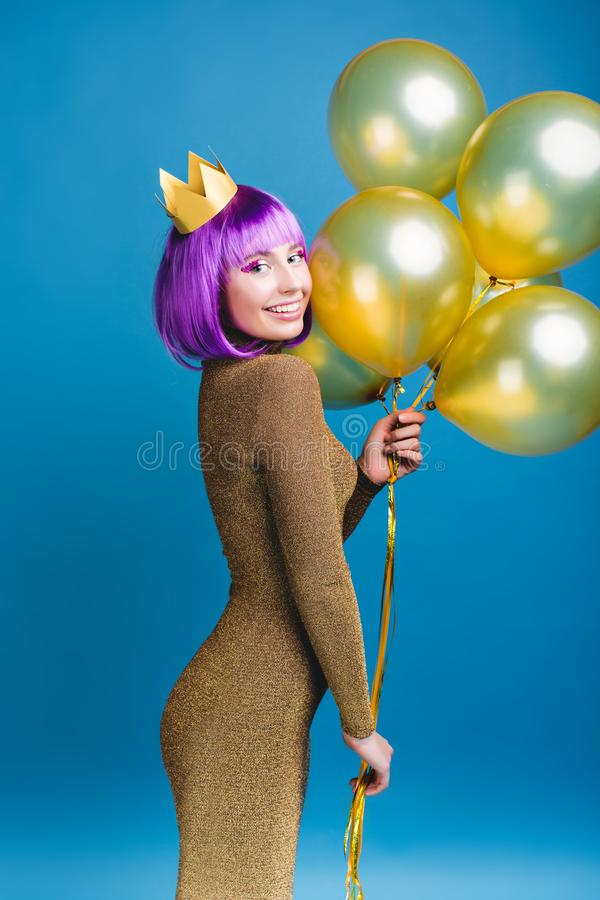 Attractive joyful young woman in luxury fashionable dress celebrating great party on blue background. Golden balloons royalty free stock images