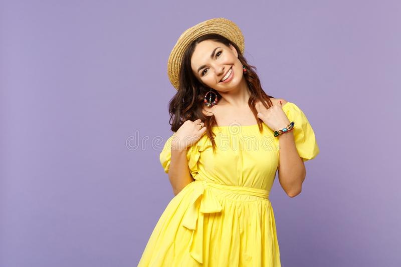Attractive joyful young woman in yellow dress, summer hat standing, looking camera isolated on pastel violet wall royalty free stock photo