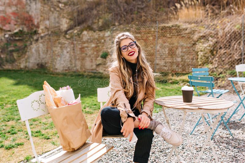 Attractive lady in beige coat sitting with comfortable pose in park after food shopping. Charming female model in. Glasses sits waddling and smiling to the stock photo