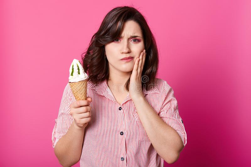 Attractive lady looks at camera, holds fresh milk ice cream, keeps hand on cheek, has toothache. Brunette sufers from sensitive royalty free stock image