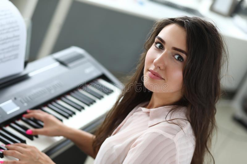 Attractive lady playing piano royalty free stock image