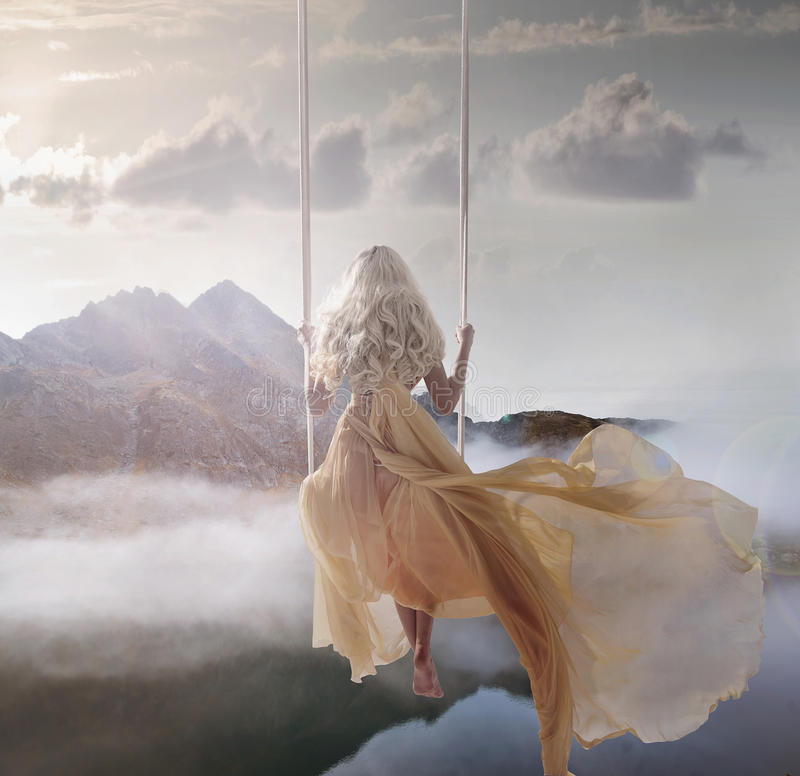 Attractive lady sitting on the swing above the calm lake stock images