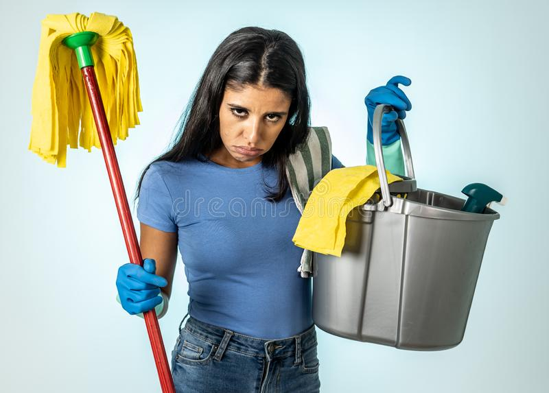 Attractive latin woman bored and restless of cleaning and house kipping stock image