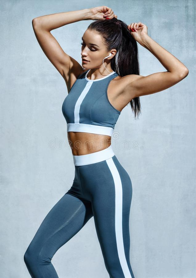 Attractive latin woman in fashionable sportswear on grey background stock images