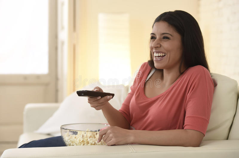 Attractive latin woman at home sofa couch laughing and smiling happy watching television. Young beautiful and attractive hispanic woman at home sofa couch royalty free stock images