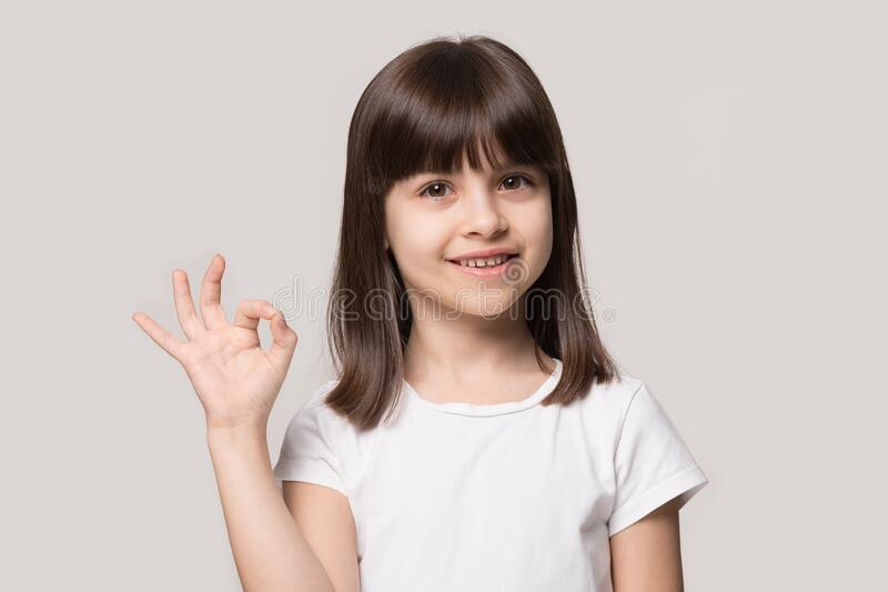 Attractive little 6 years old smiling cutie showing okay gesture. stock images