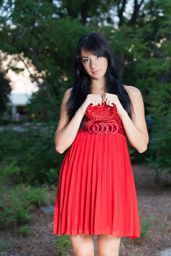 Attractive long haired brunette in red sundress posing in park royalty free stock photography