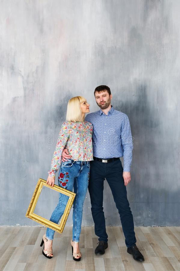 Attractive loving couple are standing near the texture wall, look at the camera and smiling. royalty free stock photos