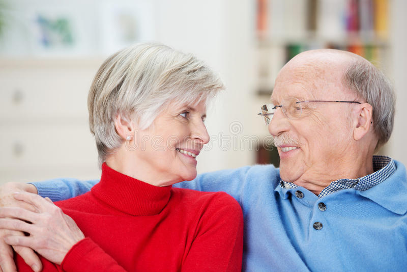 Attractive loving senior couple relaxing at home stock photos