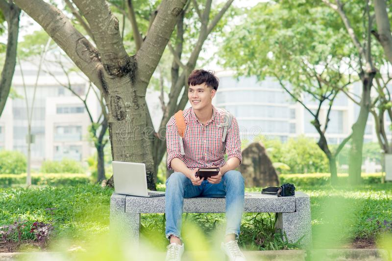 Attractive male asian student is using computer in university`s stock photo