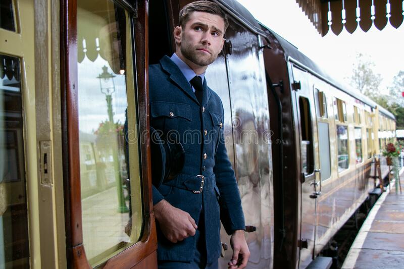 Handsome male British officer in vintage uniform at train station leaving train and looking for his partner royalty free stock photos