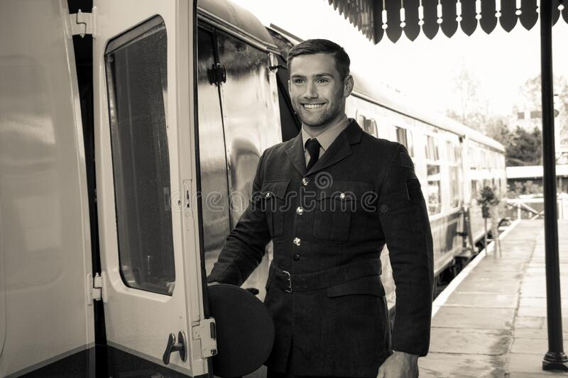 Handsome male British officer in vintage uniform at train station next to train, smiling stock images