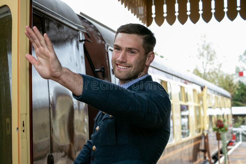 Handsome male British officer in vintage uniform at train station next to train waving and smiling stock photos