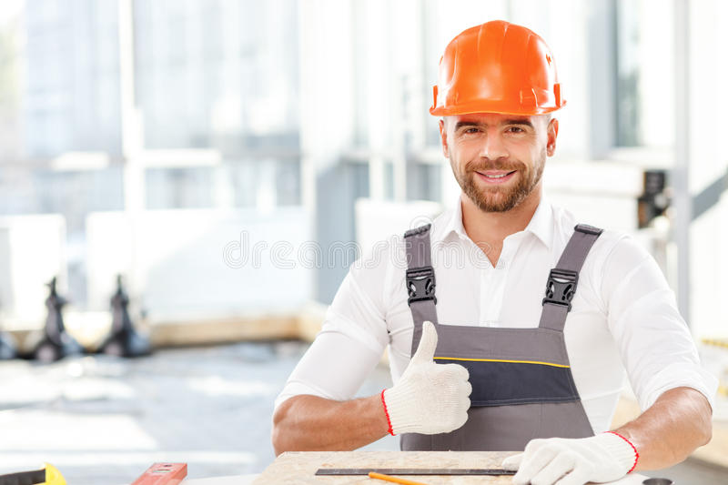 Attractive male builder is working with wooden royalty free stock photo