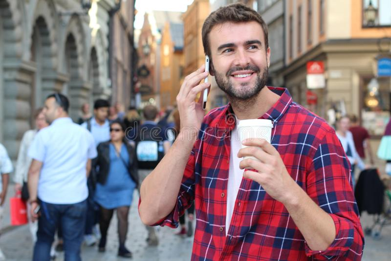 Attractive male calling by phone on a crowded street with copy space.  royalty free stock photo