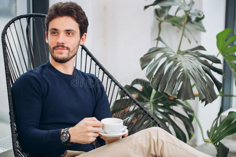Attractive male celebrity holding a cup of coffee and looking aside stock images