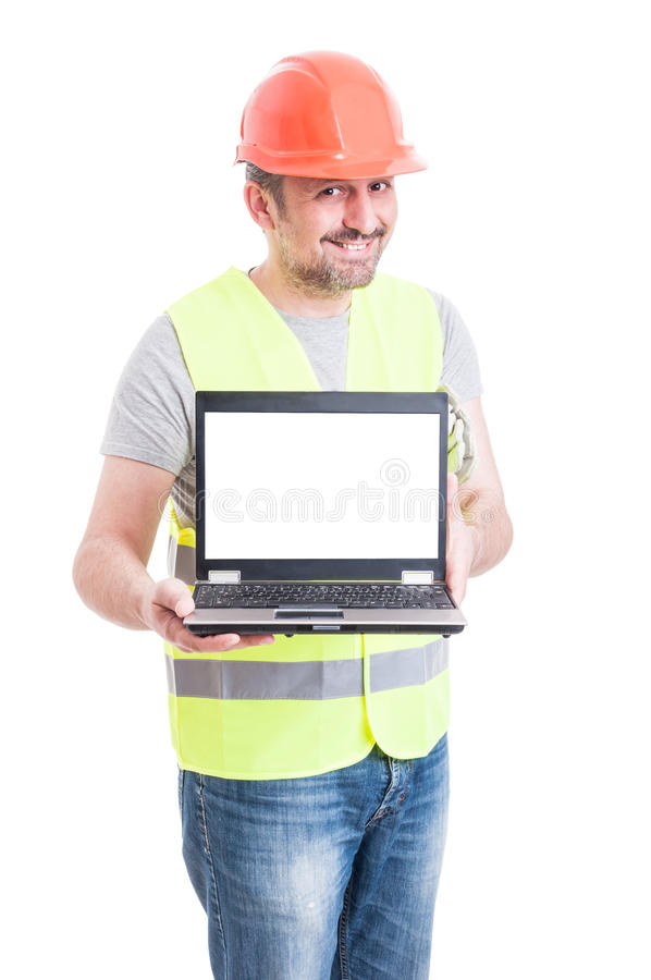 Attractive male constructor showing laptop with empty screen royalty free stock photography