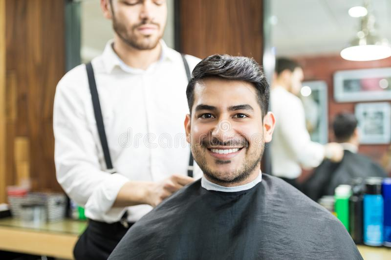 Customer Smiling While Barber Adjusting Hairdressing Cape On Him royalty free stock photography
