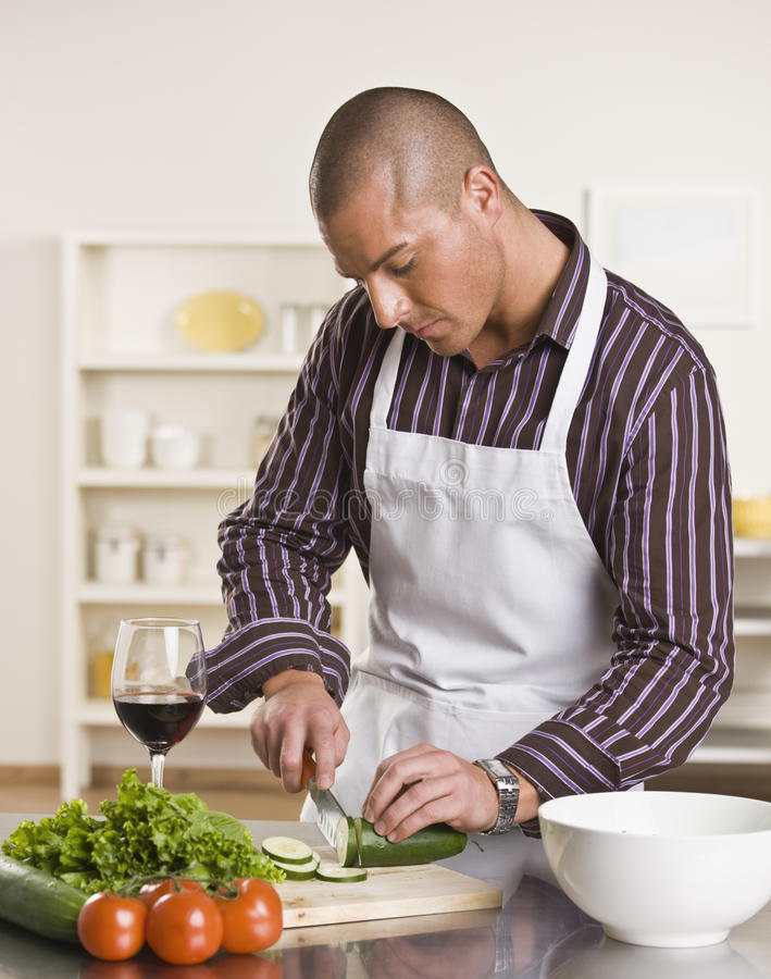 Attractive male cutting salad