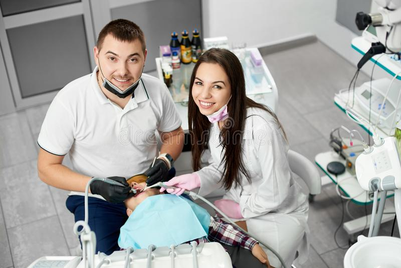 Male dentist and his pretty female assistant rae smiling to the camera while attending the teeth of their child client royalty free stock photos