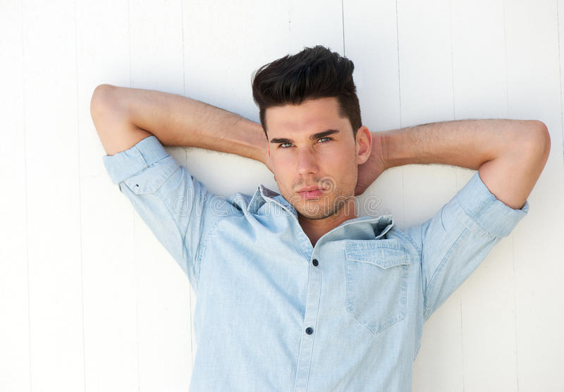 Attractive male fashion model with hands behind head. Portrait of an attractive male fashion model with hands behind head royalty free stock image