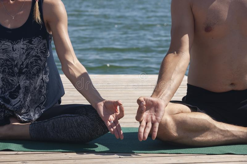 Attractive male and female practicing yoga in lotus pose close up hands. A young couple doing yoga to meditate their body and soul stock photography