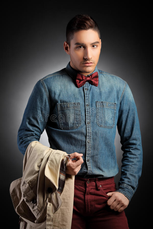 Attractive male model holding coat and posing royalty free stock photography