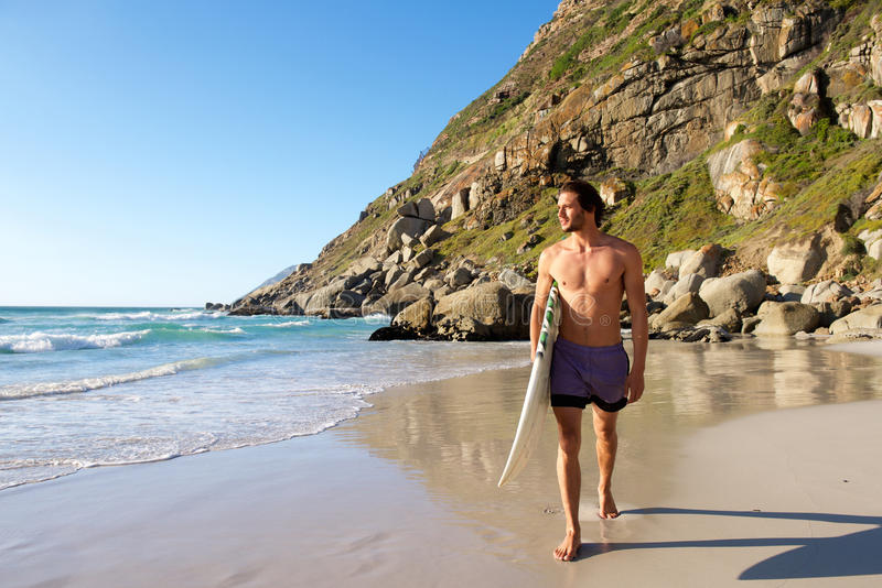 Attractive male surfer walking on beach with surfboard stock images