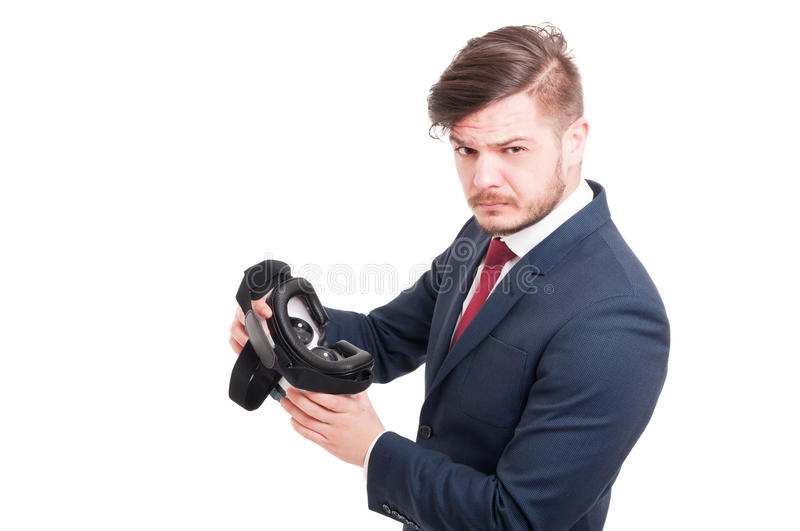 Attractive male with vr headset in hands. Being skeptic about virtual reality isolated on white stock photo