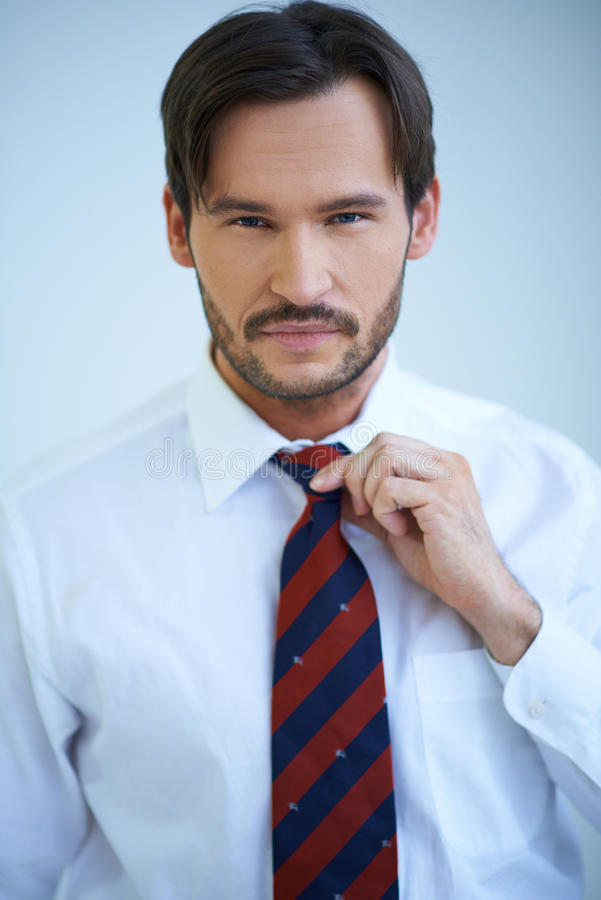 Attractive man adjusting his tie. Attractive man adjusting the knot of his tie as he stares straight ahead at the camera royalty free stock photos