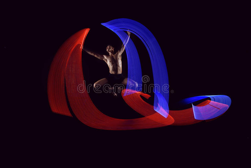 Attractive man ballet dancing with glowing lights effect stock images