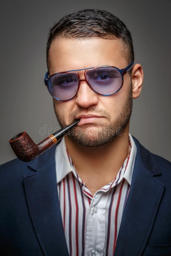 A man smoking a pipe. Attractive man in a blue sunglasses smoking a pipe stock photography