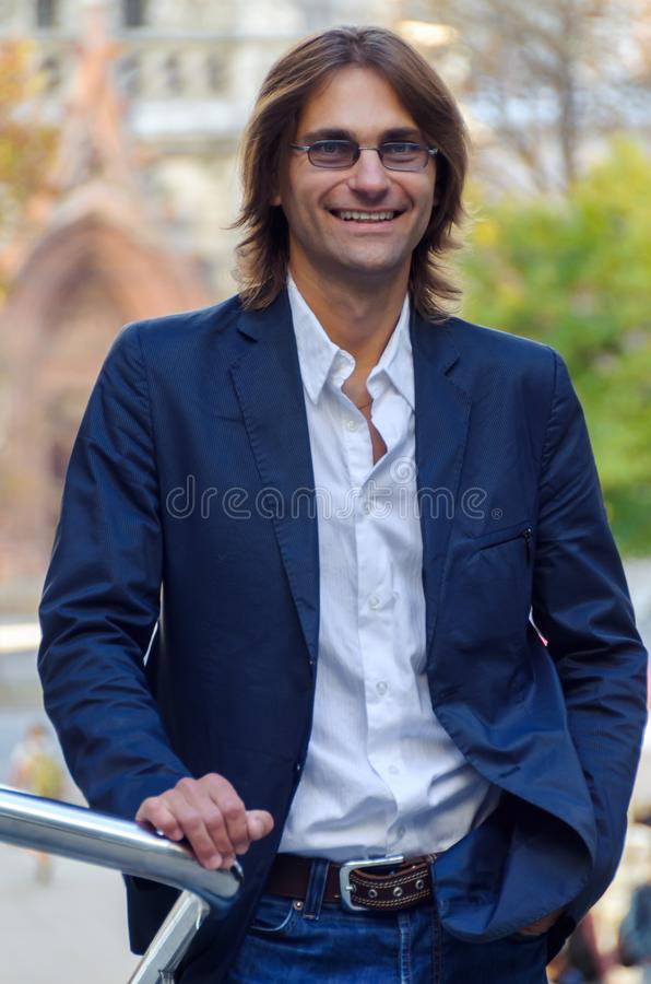 Attractive man in a business suit and glasses stands near the bu royalty free stock image