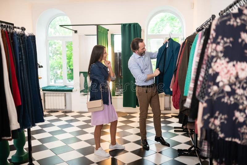 Attractive man choosing a new blazer along with his wife. royalty free stock images
