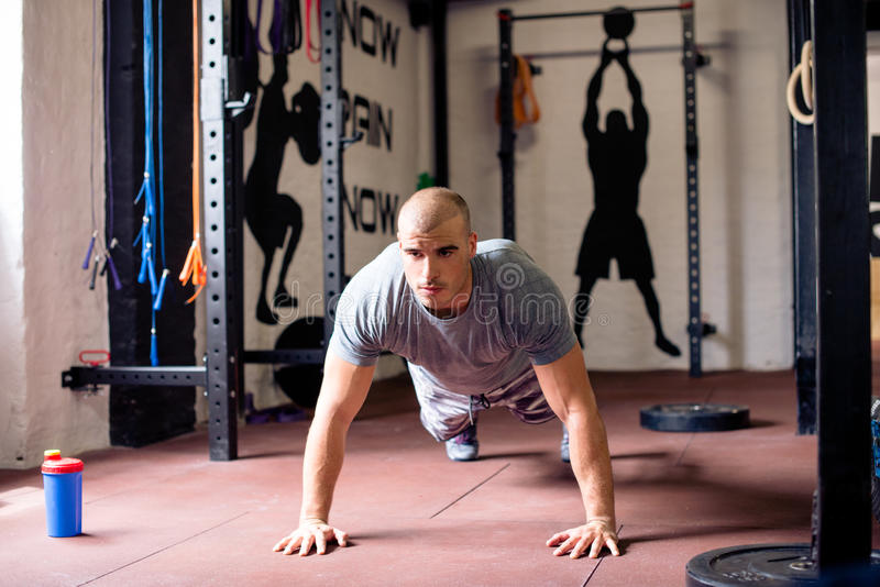 Attractive man is doing push ups. In gym royalty free stock photos