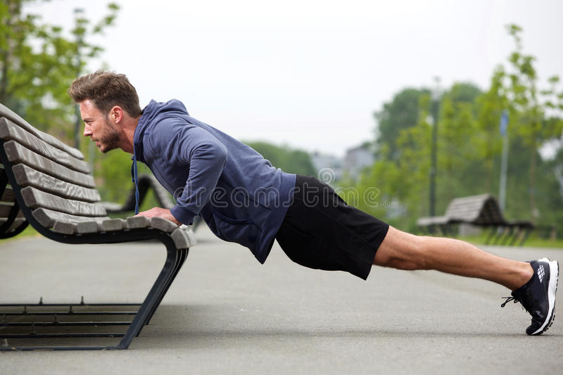 Attractive man doing pushup outside stock images