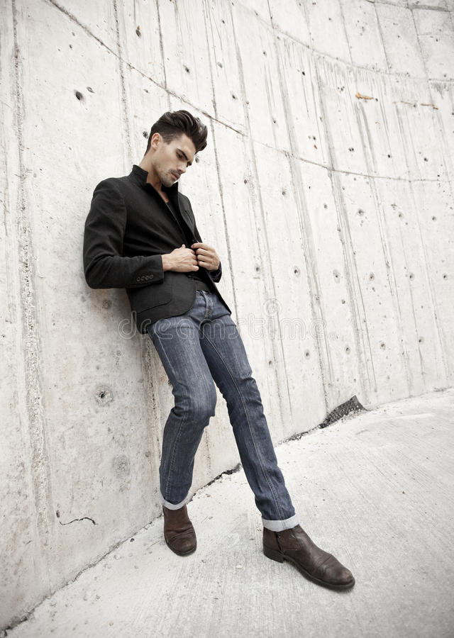Attractive man dressed in jeans and boots stock image