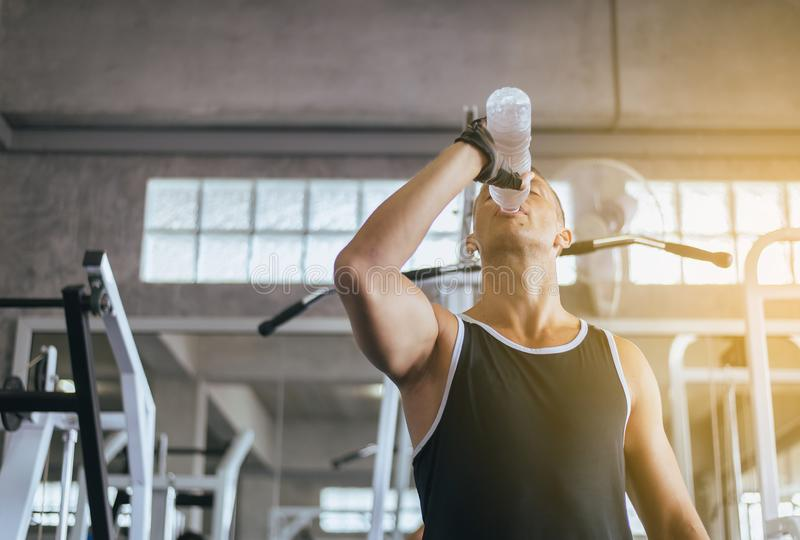 Attractive man drinking water in gym,Men break and relex after workout royalty free stock image