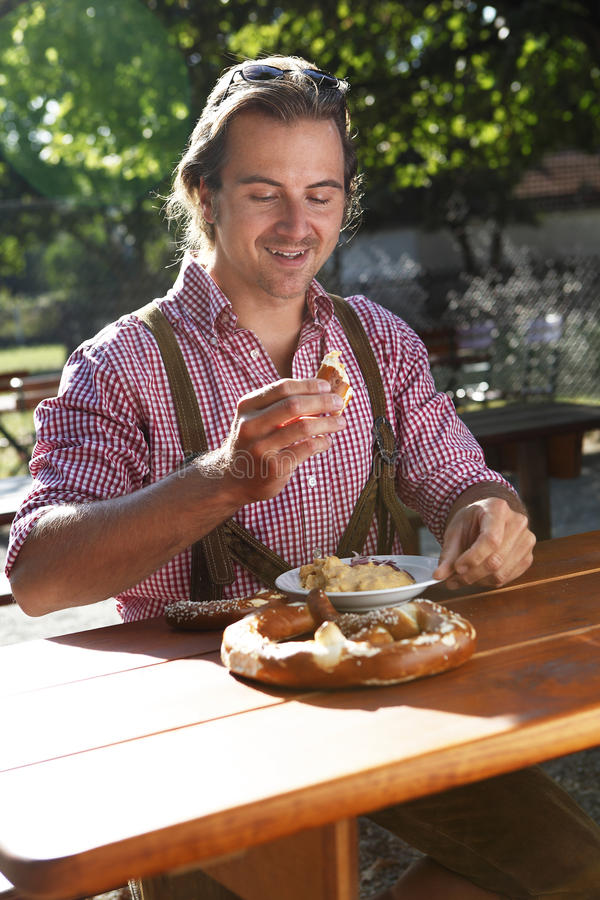 Attractive man eats traditional cheese in a Bavarian beer garden royalty free stock photos