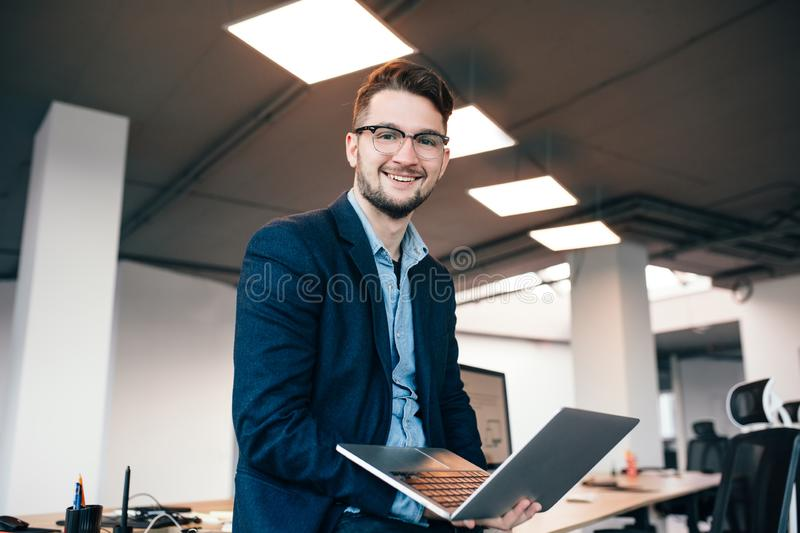 Attractive man in glassess is standing near the workplace in office. He wears blue shirt, dark jacket. He is typing royalty free stock image