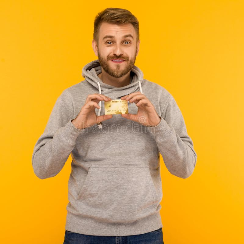 Attractive man in a gray hoodie holds a credit card in his hands on a yellow background stock image