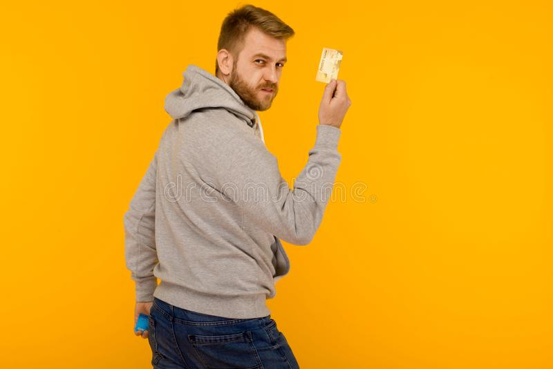 Attractive man in a gray hoodie points a finger at the credit card that is holding in his hand on a yellow background royalty free stock photos