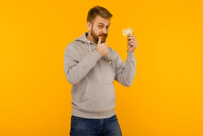Attractive man in a gray hoodie points a finger at the credit card that is holding in his hand on a yellow background stock images
