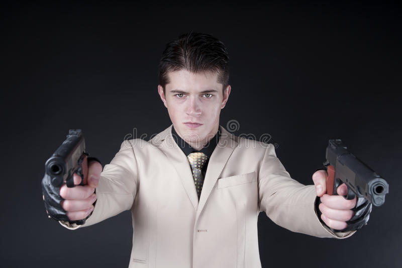 Attractive man with a gun wearing a white suit royalty free stock photos