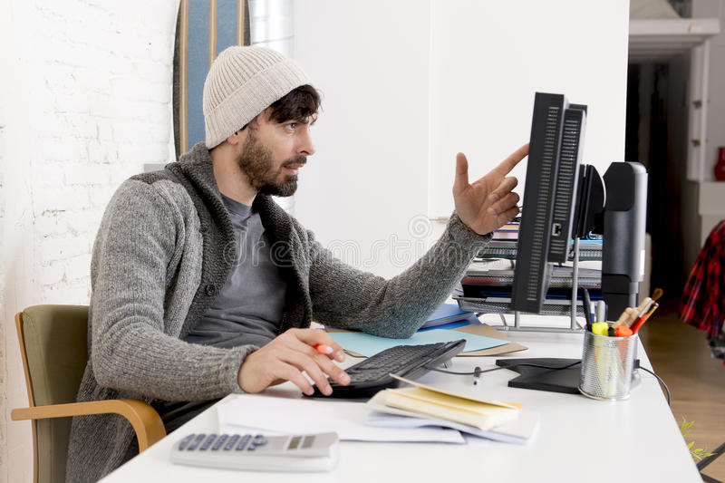 Attractive man hipste trendy businessman working desktop computer at home office. Young attractive man in hipster beanie and trendy style businessman working in royalty free stock photography