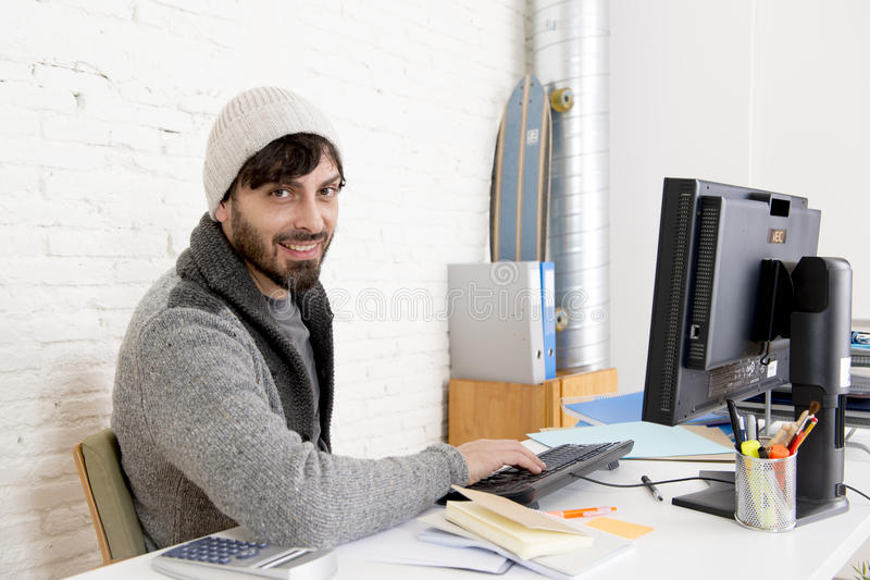 Attractive man in hipster beanie businessman working happy at office with computer. Young attractive man in hipster beanie and trendy style businessman working stock photography