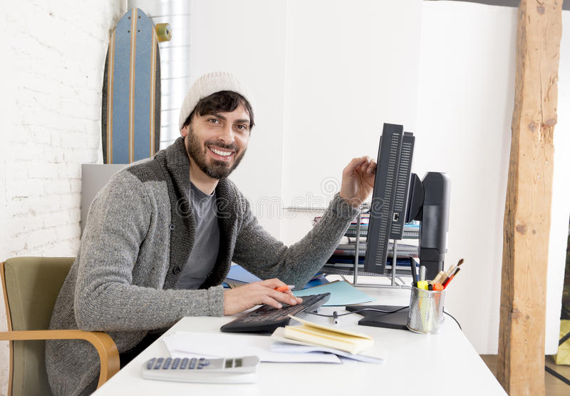 Attractive man in hipster beanie businessman working happy at office with computer. Young attractive man in hipster beanie and trendy style businessman working stock photo
