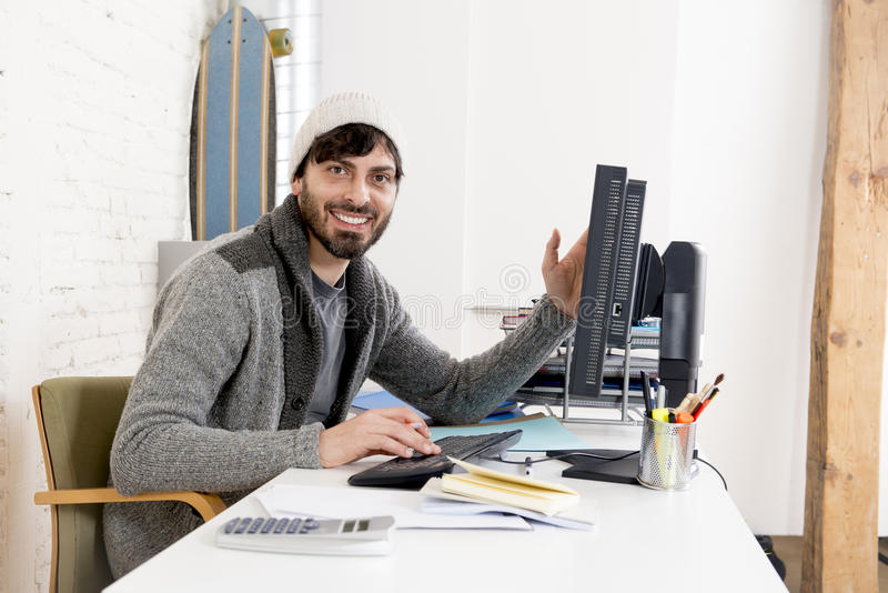 Attractive man in hipster beanie businessman working happy at office with computer. Young attractive man in hipster beanie and trendy style businessman working royalty free stock photos