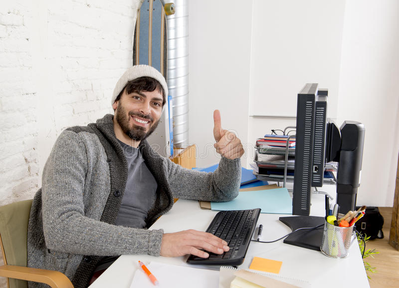 Attractive man in hipster beanie businessman working happy at office with computer. Young attractive man in hipster beanie and trendy style businessman working royalty free stock photo