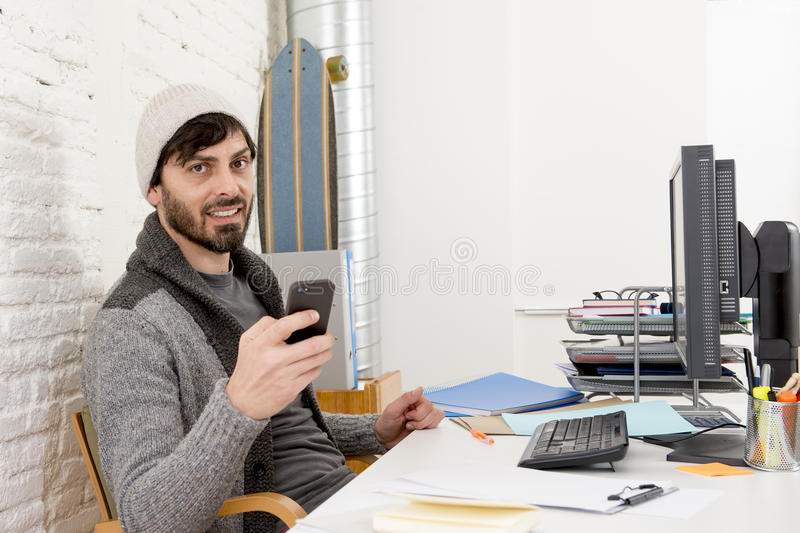 Attractive man in hipster beanie and trendy style businessman working happy at home office with desktop computer. Young attractive man in hipster beanie and stock photos
